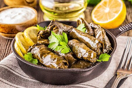 Dolma, stuffed grape leaves with rice and meat on dark background, selective focus. Imagens