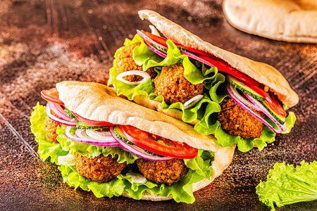 Falafel and fresh vegetables in pita bread on dark background.