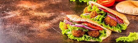 Falafel and fresh vegetables in pita bread on dark background. Stock Photo