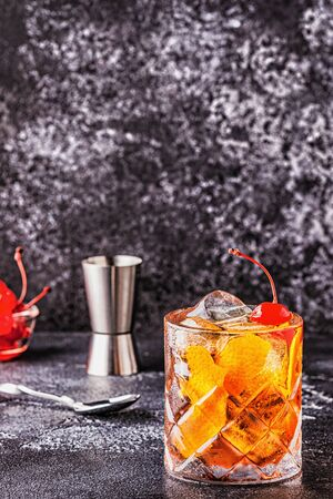 Old fashioned cocktail with cherries and orange twist, selective focus. Stock Photo