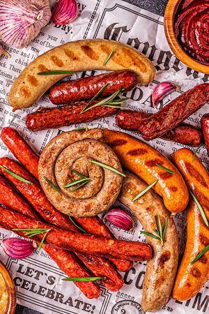 Homemade sausages grilled on a newspaper, top view. Banque d'images