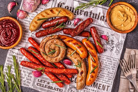 Homemade sausages grilled on a newspaper, top view.