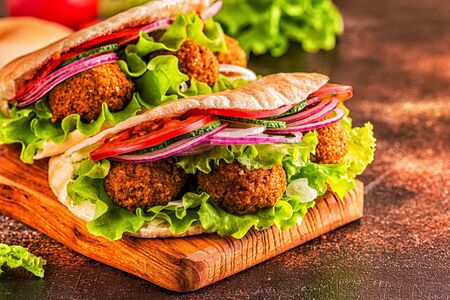 Falafel and fresh vegetables in pita bread on dark background. Imagens