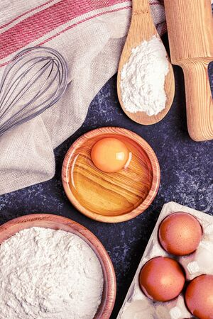 Ingredients for baking  - flour, wooden spoon, rolling pin, eggs. Top view, copy space.
