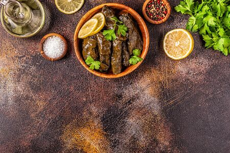 Dolma, stuffed grape leaves with rice and meat on dark background, top view. Imagens