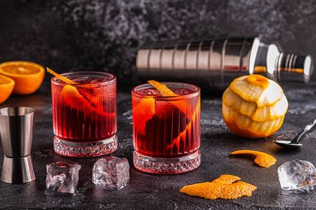 Negroni cocktail with orange peel and ice, selective focus.