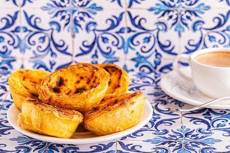 Egg tart, traditional Portuguese dessert, pastel de nata. Azulejo tile background.