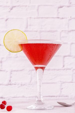 Glass of cosmopolitan cocktail decorated with lime, selective focus