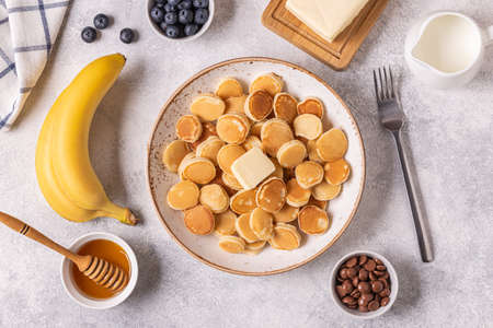 Trendy breakfast with mini pancakes and butter, top view. Archivio Fotografico