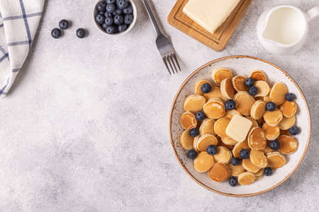 Trendy breakfast with mini pancakes and blueberries, top view.