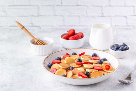 Tiny pancakes with strawberries and blueberries for breakfast. Selective focus. Archivio Fotografico