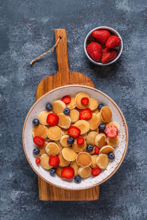 Tiny pancakes with strawberries and blueberries for breakfast. Top view.