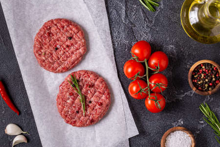 Fresh raw meat burger cutlet with herbs and spices on the black stone board, top view Stock fotó
