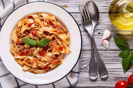 Traditional italian pasta bolognese on a white plate on a wooden background, top view.