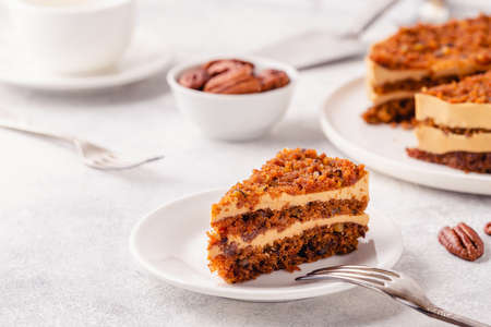 Vegan homemade carrot cake with pecans, on a light background.