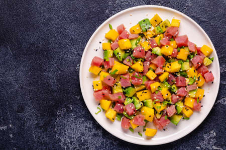 Tuna mango avocado salad tartare served with green onions and sesame seeds.