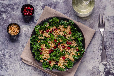 Healthy raw kale and quinoa salad with cranberry and pine nut. Top view.