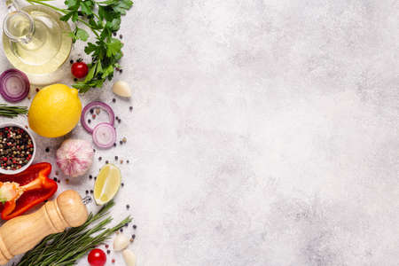 Herbs and condiments on light stone background. Top view with copy space. Reklamní fotografie