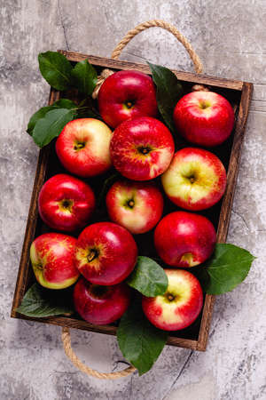 Ripe red apples in wooden box. Top view with copy space.