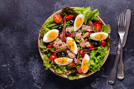 French salad Nicoise with tuna, eggs, green beans, tomatoes, olives, lettuce and anchovies.
