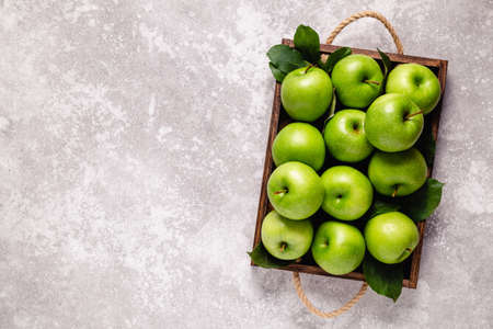 Ripe green apples in wooden box. Top view with copy space.