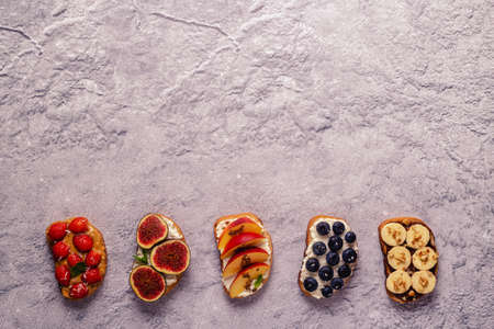 Homemade summer toast with cream cheese, nut butter and fruits and berries, top view.