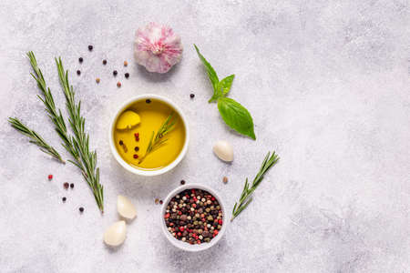 Herbs and condiments on light stone background. Top view with copy space. Imagens