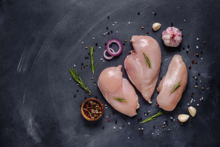 Raw chicken fillet with spices and herbs, top view. Imagens