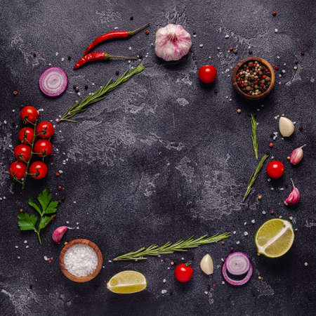 Herbs and condiments on black stone background. Top view with copy space.