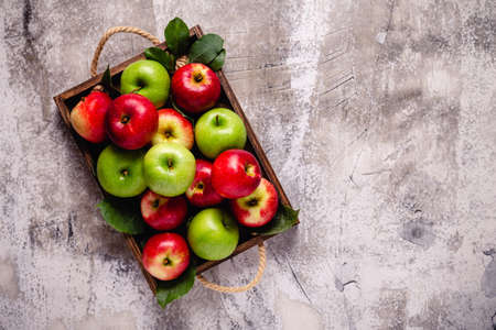 Ripe red and green apples in wooden box.