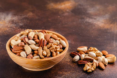 Various Nuts in wooden bowl on dark background.