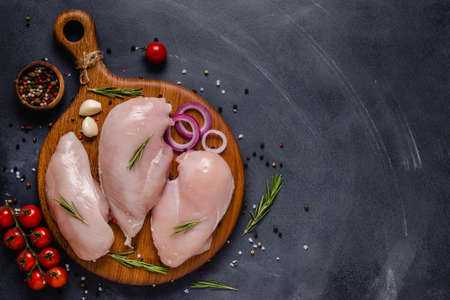 Raw chicken fillet with spices and herbs, top view. Reklamní fotografie