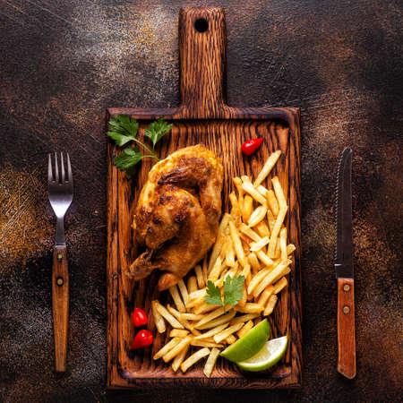 Half roasted chicken Piri Piri with french fries, top view Reklamní fotografie