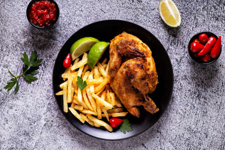 Half roasted chicken Piri Piri with french fries, top view Imagens
