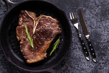 Grilled beef steak with spices in a frying pan, top view
