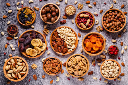 Various Nuts and dried fruits in wooden bowls, top view.