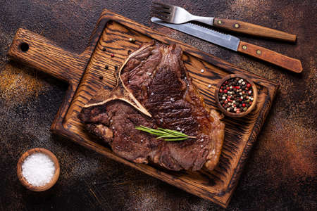 Grilled beef steak with spices on a wooden board, top view.