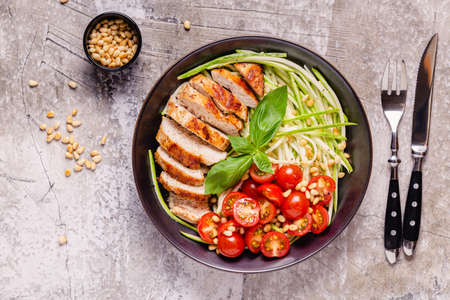 Fried chicken fillet and fresh vegetable salad of tomatoes, zucchini and pine nuts. Chicken meat salad. Healthy food. Ketogenic diet.