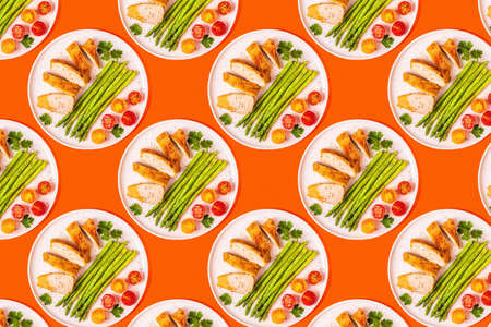 Pattern of roasted chicken breast with asparagus and tomatoes on the plate.