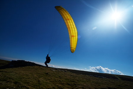 Paragliders on a mountain top preparing to take flight flying over a mountain valley in summer Stock Photo