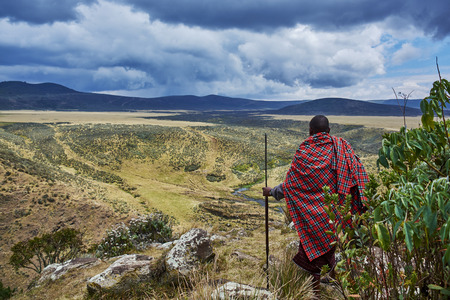 Hike in Olmoti Crater,  near Munge River  Ngorongoro Conservation Area Nationnal park Highlands with Masai Guide wearing traditionnal red blanket