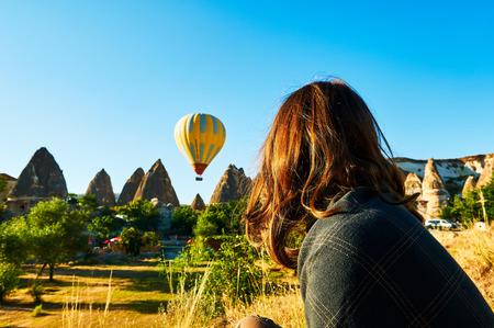 Les femmes à la recherche de montgolfières sur ciel bleu turquoise dans la ville de cappadoce au lever du soleil Banque d'images - 101015785