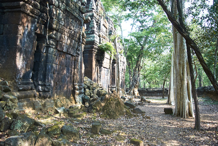 Prasat Chrap has two concentric enclosures. In the center, three tall laterite towers stand in a row, all of them lost their front walls. There are two more brick sancturies (or maybe library buildings) facing the principal group, but only remnants left.
