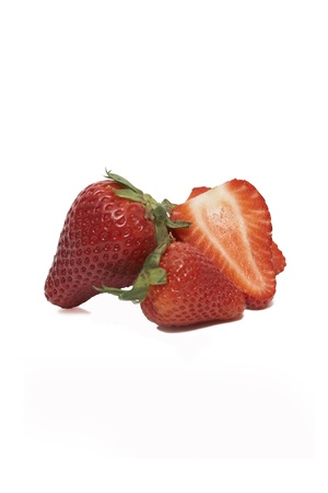 unsliced: A group of sliced and unsliced strawberries isolated on a white background.