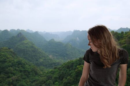 mountain pass: Young woman is looking down from the mountain top, Vietnam Stock Photo