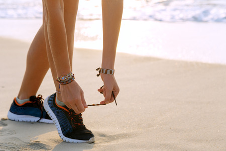 Healthy runner woman tying running shoes laces getting ready for beach jogging. Female athlete living a fit and active life Stock Photo