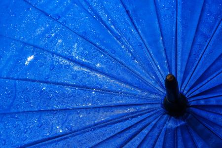Umbrellas filled with rain drops .