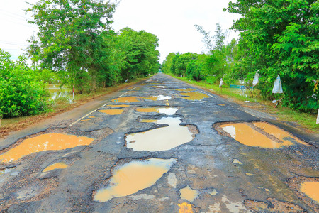 blacktop: Road with potholes from the flood. Stock Photo