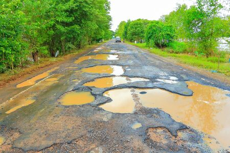 Road with potholes from the flood. Stock Photo