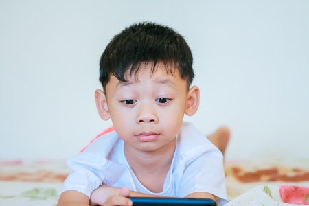 Children hands hold smartphone for playing and education.